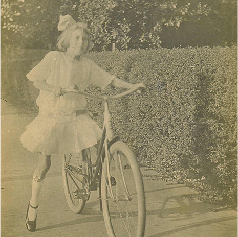 Eudora Welty as a young girl in Jackson, Mississippi, around 1916, riding a bicycle on a hedge-lined sidewalk in a lacy dress, a hair bow, and Mary-Jane shoes.