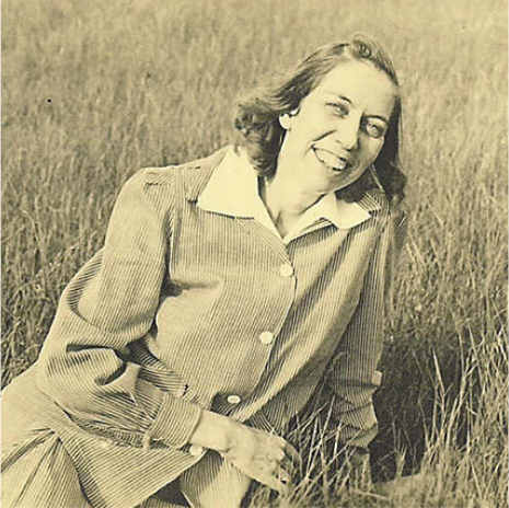Eudora Welty in her mid-twenties sitting in a grassy field and smiling in a 1930s pin-striped skirt suit and white collared blouse.