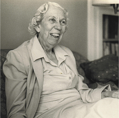 Author Eudora Welty in her later years, seated indoors and laughing, in a dress and blazer.