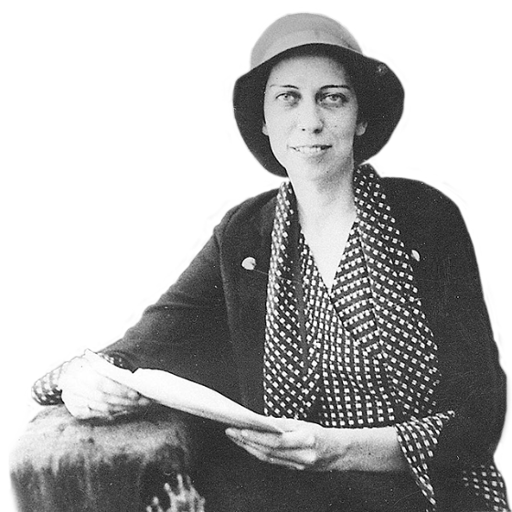 Eudora Welty around age twenty in a cloche hat, geometric patterned blouse, and matching trimmed blazer, holding a letter in an envelope.