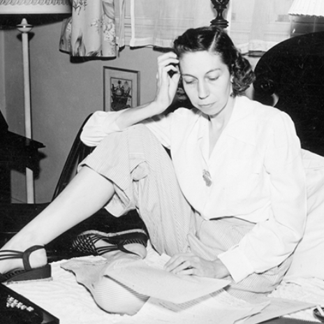 Author Eudora Welty sitting on her bed in a blouse and striped slacks, surrounded by papers and a typewriter, reading a manuscript, with one hand resting on her head.