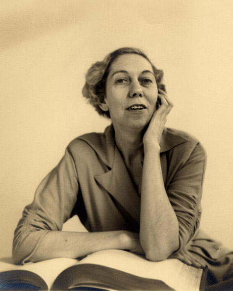 Eudora Welty as a young woman seated behind a large open book, with one arm folded across the pages and one hand at her cheek.