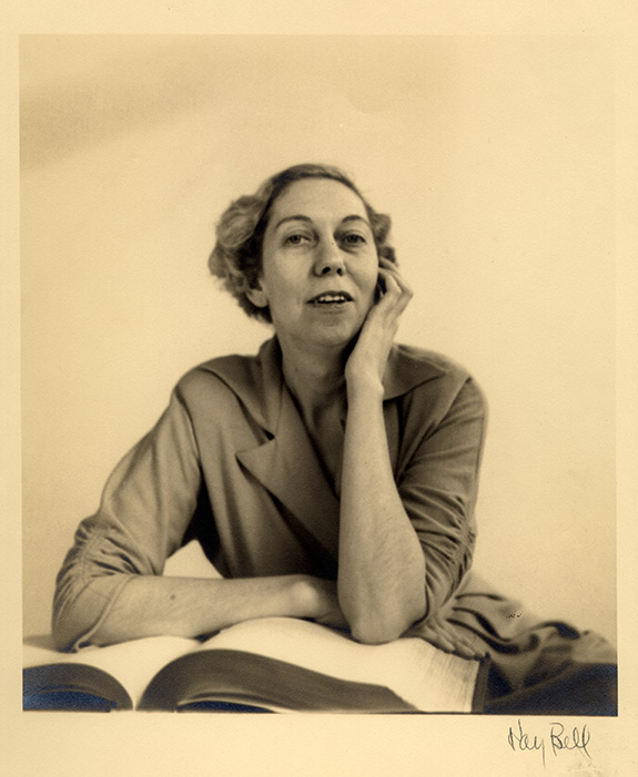 Portrait of Eudora Welty as a young woman seated behind a large open book, with one arm folded across the pages and one arm under her chin, photographed by Kay Bell.
